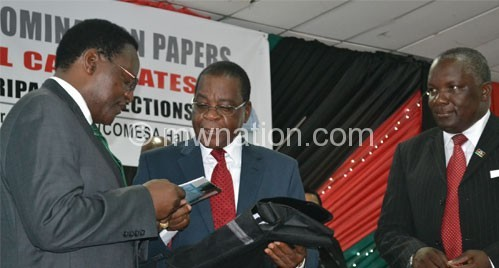 Mbendera (C) presenting the Code of Conduct and other documents to Chakwera (L) as Msowoya looks on