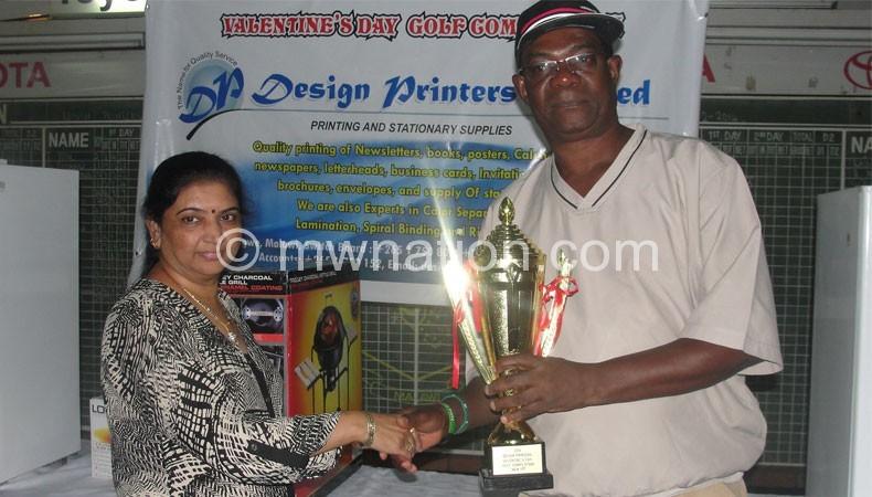 Design Printers representative (L) presents a trophy to Mkandawire