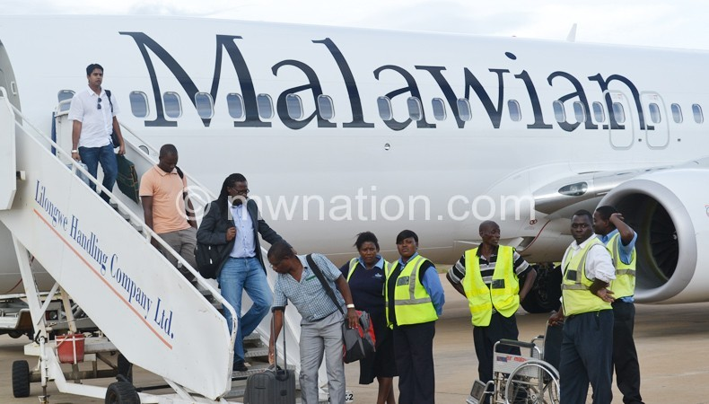 Passengers alight from Malawian Airlines plane