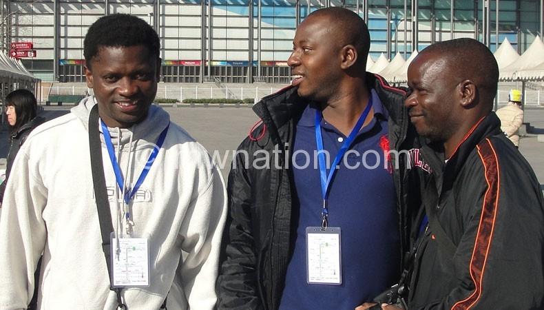 Kaminjolo, Kampala and Bernard Ndege pose outside the Bird's Nest
