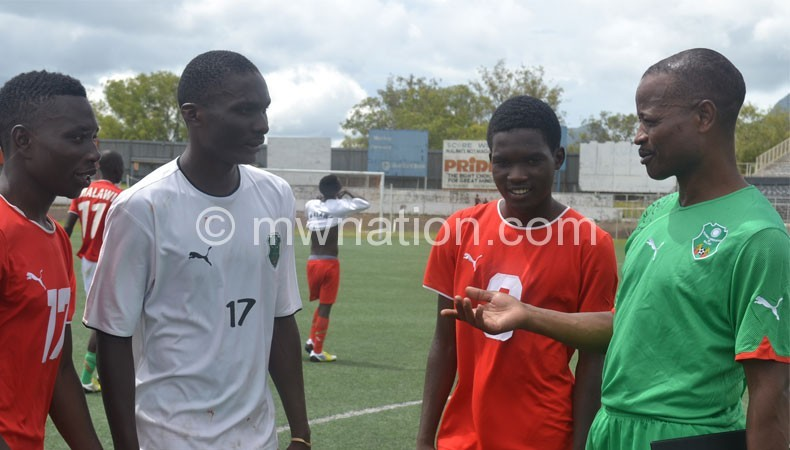 Mtawali (R) shares notes with some of his players