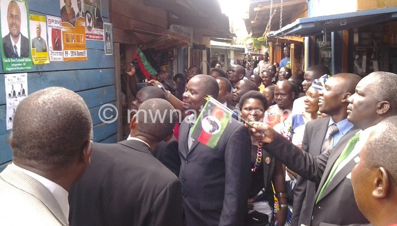 Msowoya (with a flag) taking a look at campaign posters