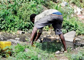 Cashing in: A casual labourer drawing water to sell to vendors at the market general usage