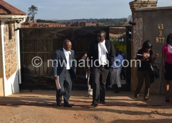 Enock Chibwana (L), prosecutors in the Directors of Public Prosecutions (DPP), Malunda (2nd L) and journalists leaving Mphwiyo's house yesterday