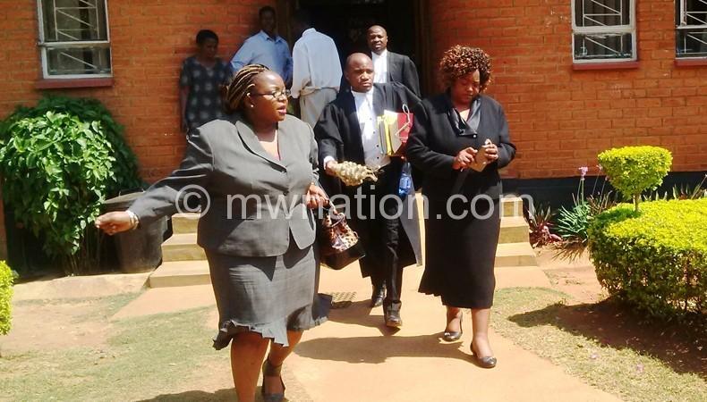 Senzani (L), her lawyer (2ndL) and sympathiser leaving a courtroom
