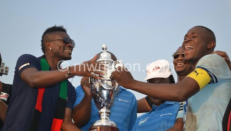 Silver captain Lucky Malata (R) receives a trophy from Asamoah Gyan