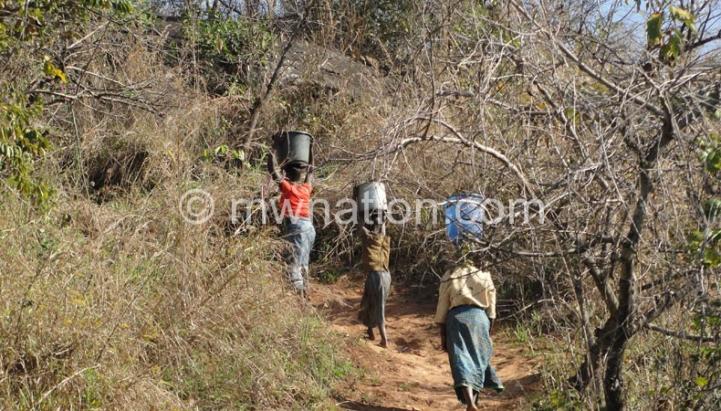 Village women endure bad terrain and long distances to fetch water for home use