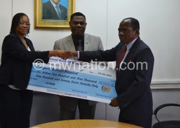 Banda receiving a dummy cheque from Kayambo as Press Trust Press Trust CEO Patrick Luhanga looks on