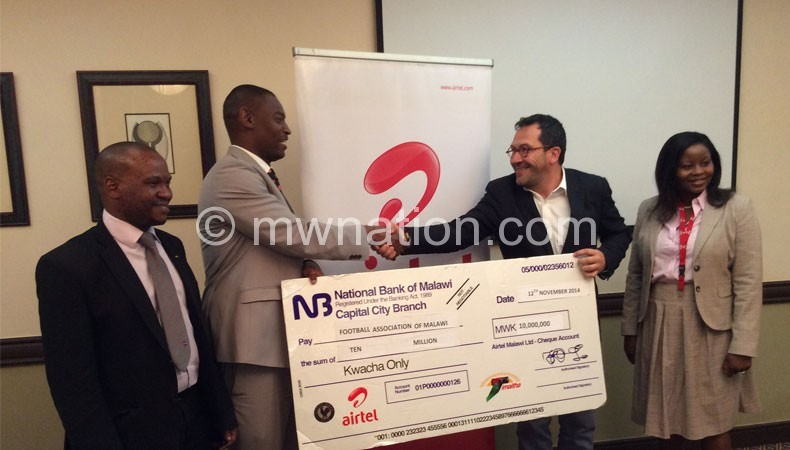 Nyamilandu (2ndL) receives a dummy cheque from Schlittke as FAM CEO Suzgo Nyirenda (L) and Airtel head of enterprise Rachel Mijiga look on