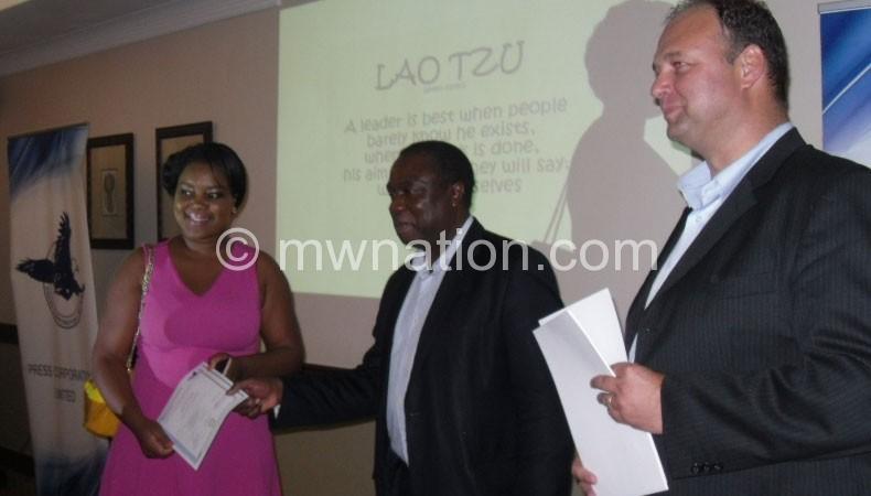 Chikaonda (C) handing over a certificate one of the graduates
