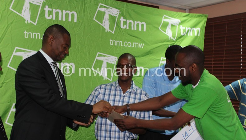 Nyamilandu (L) receives the cheque from Makata (C) and TNM marketing manager Madalitso Jonazi