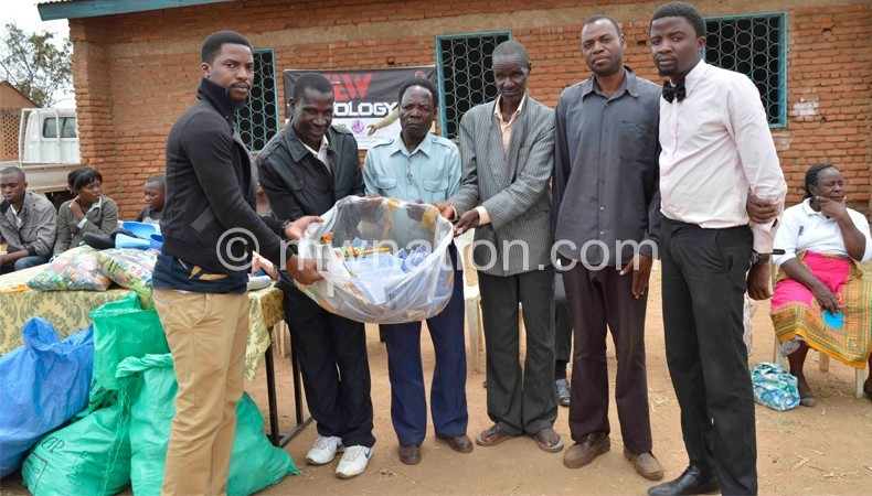 Jew Chapomba (R) and Young Kay presenting items to community elders in Chiradzulu