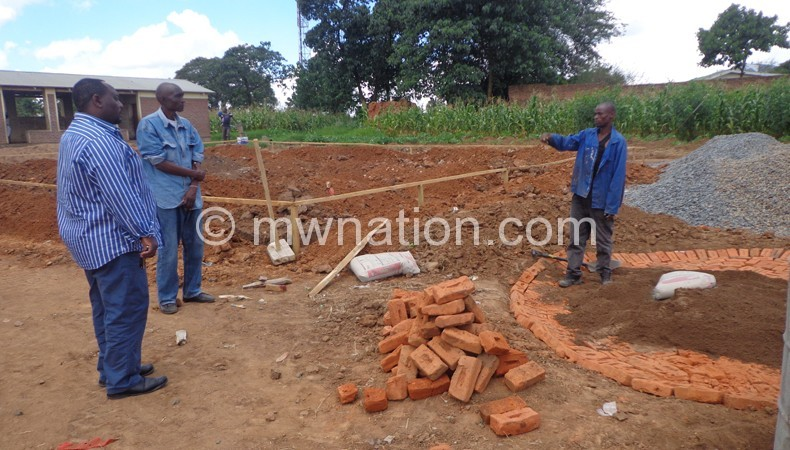 Flashback: Construction workers briefing Masangwi (L) on progress of the project