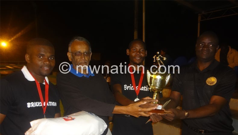 Bricks captain Makaka (C) receives trophy from Meet board member Daulos Mauambeta (R) and Sports Council board member Khrishna Achuthan
