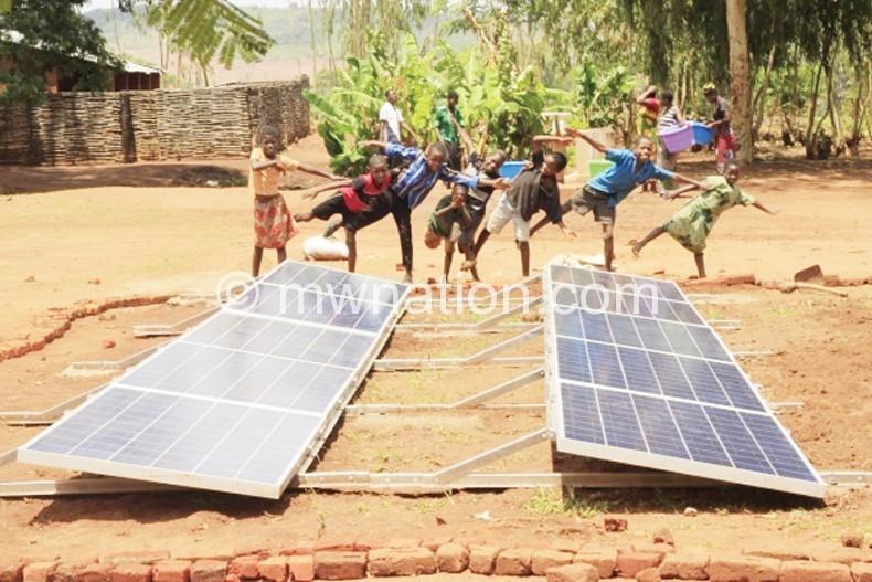 Children dance in front of solar panels