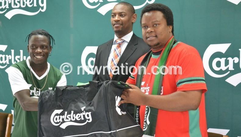 Chirwa (R) presents a travelling  bag to Kamwendo (L) as Nyamilandu looks on