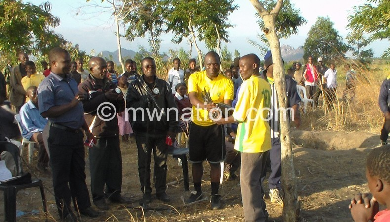 Kamwagha(in black shorts)  handing over torches