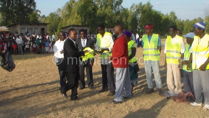 Njoloma (L) handing over reflector jackets to Kandulu (in maroon jacket)