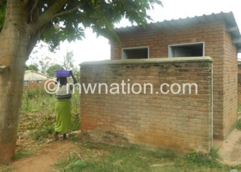 A woman going to take a bath in the toilet at Khonjeni Health Centre