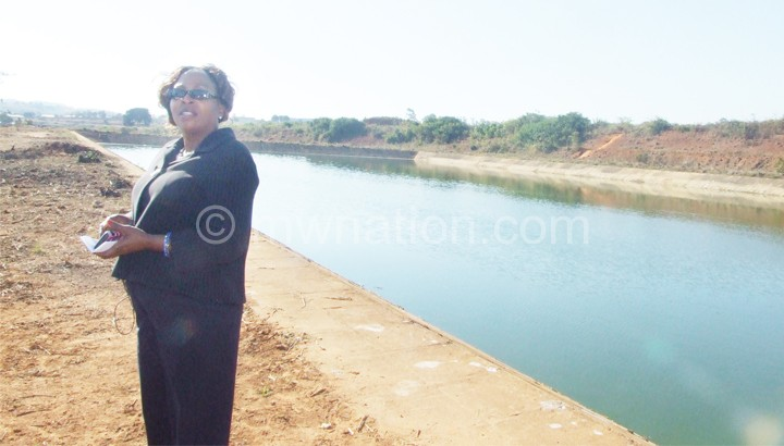 Nyirenda poses in front of one of the ponds linked to the sewerage system