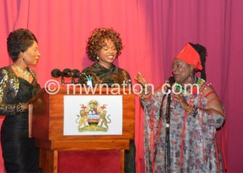 Mutharika (L) joins Chidzanja-Nkhoma in song as Chilima (C) looks on