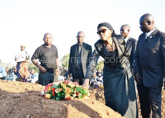 Nyondo's wife laying a wreath on his grave