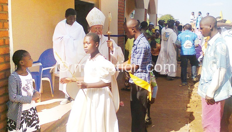 One of the members of Holy Family church greets Pagan  after the opening and dedication of the church