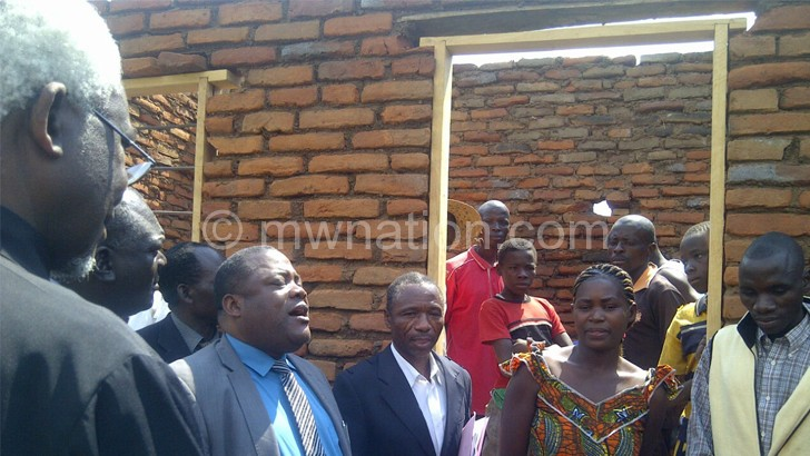 Chibingu(in blue shirt) inspecting one of the buildings in Karonga