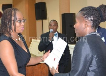 Honoured: Banda receiving her acertificate of  recognition from Chiumia (R)