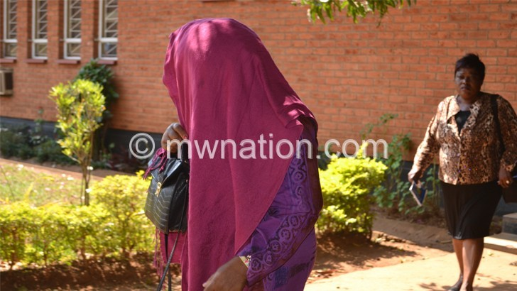 Katengeza hides her face from cameras de