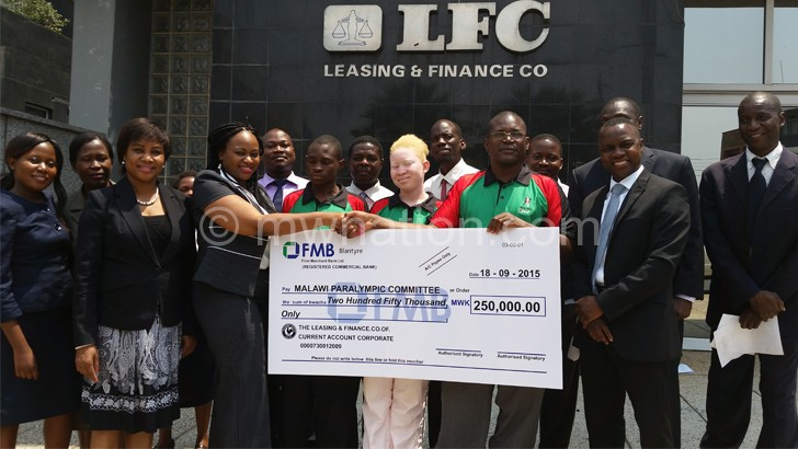 LFC's Sithembile Sisya (2nd L) presents cheque to Chiutsi as other officials look on