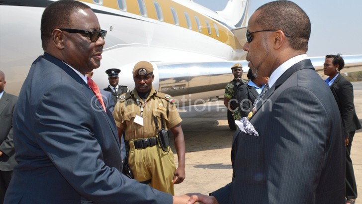 Welcome back home: Vice-President Saulos Chilima seems to be telling Mutharika on arrival on Sunday