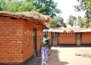 A woman walks past some of the houses that self-boarding students use as hostels