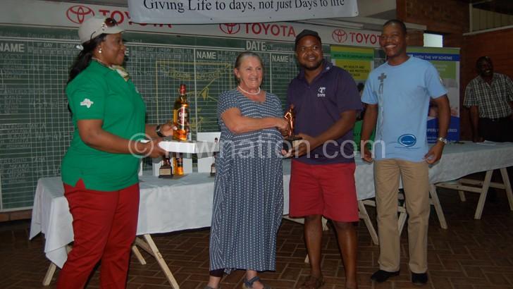 Jenette Johnson, head teacher of Bishop Mackenzie International School, presents the trophy to one  of the Masm team members as Margaret Kubwalo-Chaika (L) looks on