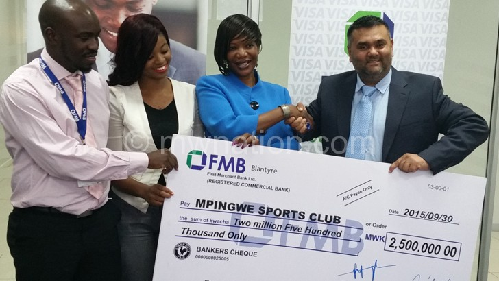 FMB's Mataka (2nd R) presents a dummy cheque to Wagot (R) as other FMB officials look on