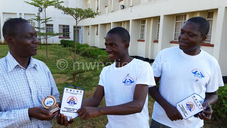 Banda (C) present his trophy to Munthali (L)  as Nkhoma looks on