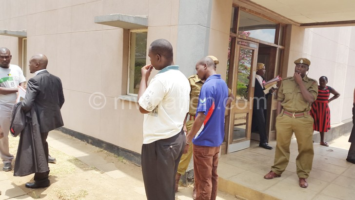 Some of the suspects and their lawyers confer under the watchful eyes of prison warders