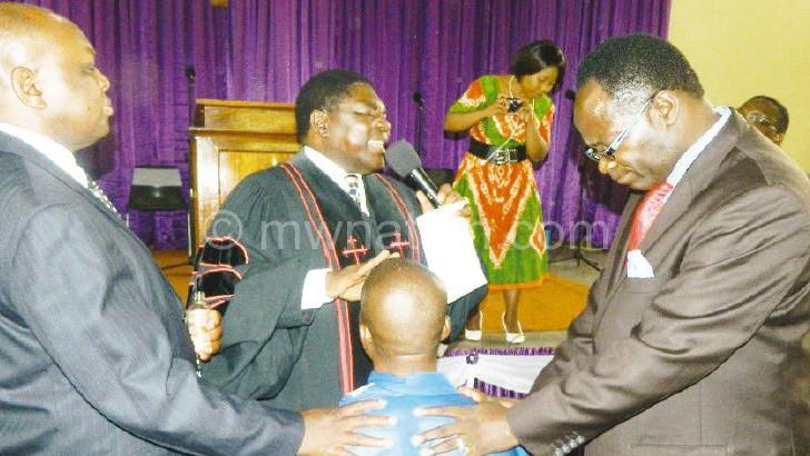 Mbewe (C) consecrates Mzumara as bishop