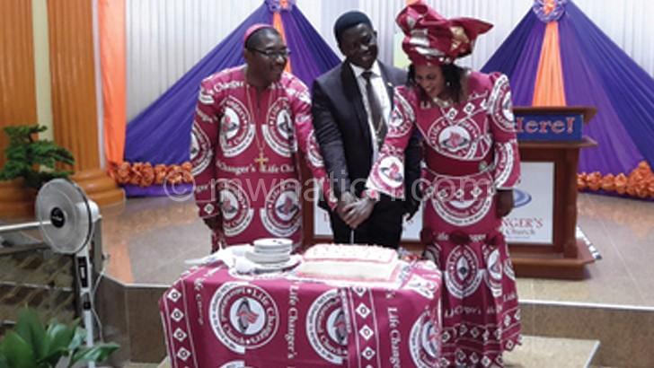 Adebayor(L) cutting the cake with his wife