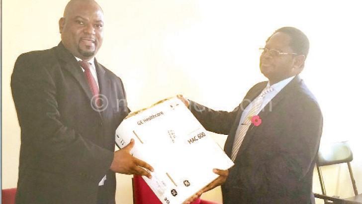 Nthakomwa (L) presents one ECG machine to Magwira at KCH on Friday