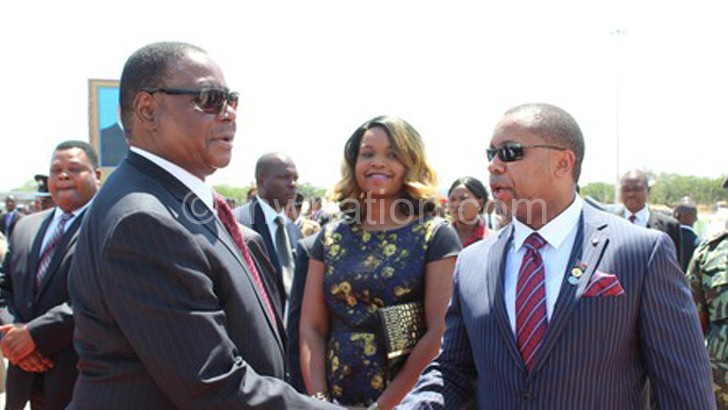 Chilima (L) welcomes Mutharika as  he arrives from a foreign trip