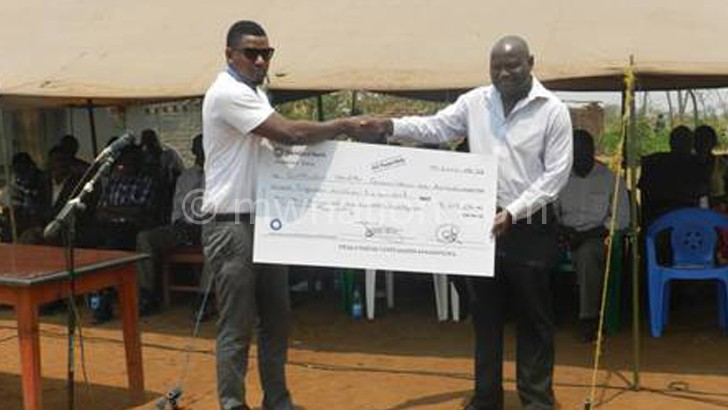 Chidaya (L) presenting a dummy cheque to  Banda