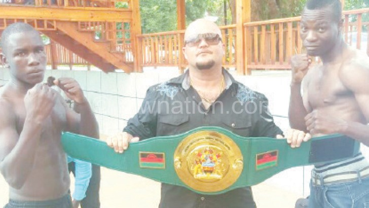 Masamba (R) and Msoliza (L) size up against each other as  Rousseau holds the belt