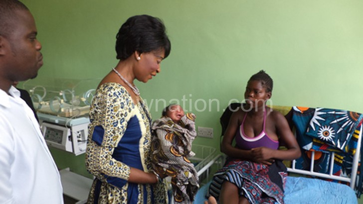 First Lady Gertrude Mutharika cradles one of the Christmas babies at Monkey Bay Community Hospital