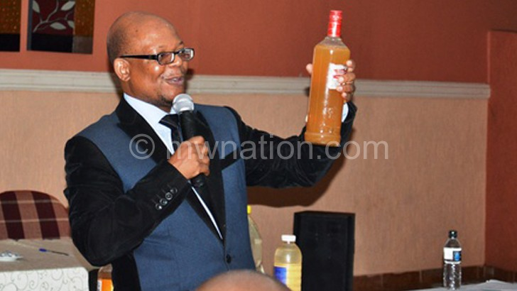 Mwanza shows a bottle of dirty tap water
