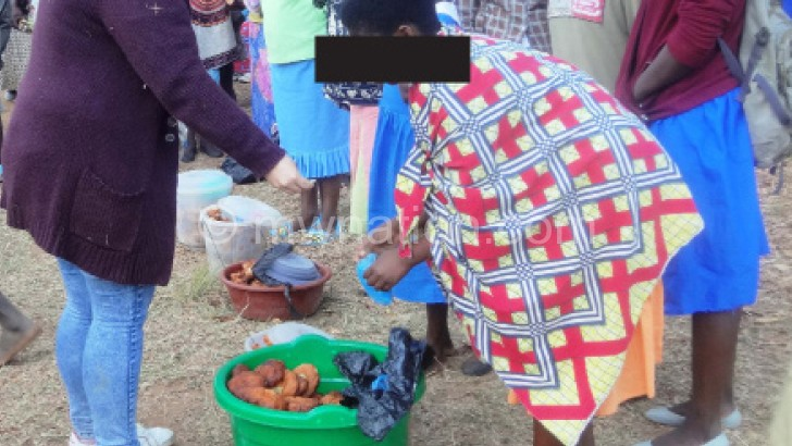 A young girl (R) and others (in school uniform) selling fritters