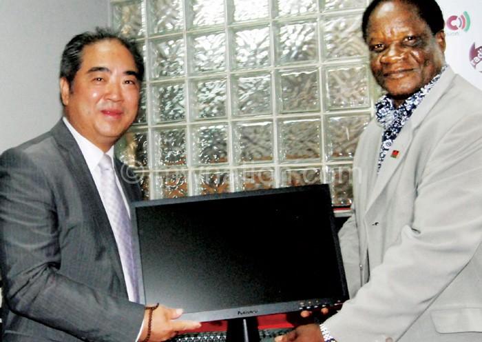 Zhang (L) presents a computer to Banda