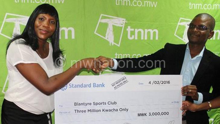 Makata (R) presents a dummy cheque to Muguvu-Karuku