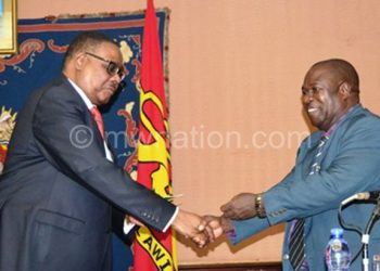 Mutharika greets Wiseman Chijere Chirwa during a meeting with media managers and owners over ATI