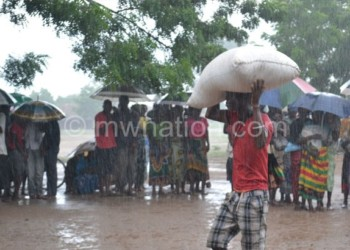 A man braves the rain to take his food home